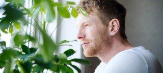 Mann i hvit t-skjorte titter ut av vindu med plante i forgrunnen.
