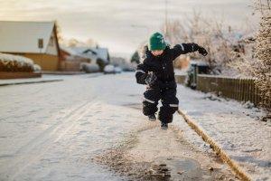 En gutt leker i snøen