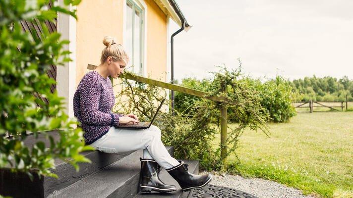 En dame som sitter med en laptop i fanget på trappa utenfor huset sitt.