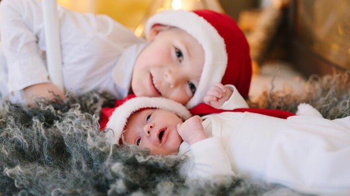 Liten gutt og baby med nisselue som ligger på et saueskinn.