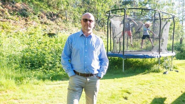 Jan-Henrik Kulberg ute i hagen med de to barna sine på trampoline i bakgrunnen.